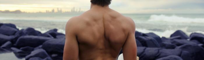 La espalda de un hombre en la playa que ha realizado el tratamiento de depilación de espalda para hombres con láser