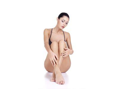 mujer mostrando su cuerpo, sentada y con las piernas cruzadas