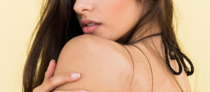 Una mujer joven de espaldas tocándose el hombro depilado en Láser Definitive, una clínica de depilación láser en Granada