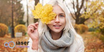 una mujer en un bosque tapándose un ojo con una hoja amarilla